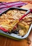 Potatoes au gratin with sautéed onions, with a selected meat